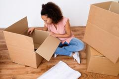 Desperate and tired woman during home relocation Stock Photos