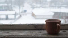 Snow falling on a cup on old wooden window sill Stock Footage