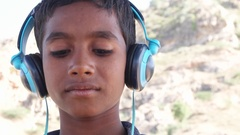 Indian boy listening nodding dancing and enjoying music on headphones with a sma Stock Footage