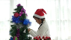 Beautiful Asian girl hanging decorative toy on christmas tree,slow motion Stock Footage