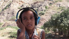 Lovely little Indian listening to music on big headphones and jumping and dancin Stock Footage