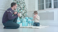 Happy father with his son sitting near the Christmas tree and drinking hot tea Stock Footage