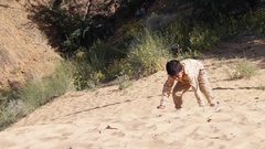 Cute Indian kid running in the sand towards the camera  Stock Footage
