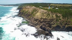 Slow rise above Cape Schanck lighthouse and the ocean waves on bright s Stock Footage