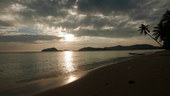 Sunset over tropical beach with winding palm and moody sky. Stock Footage