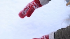 Female hands in knitted mittens making snowball Stock Footage