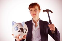 Composite image of businesswoman breaking piggy bank Stock Photos