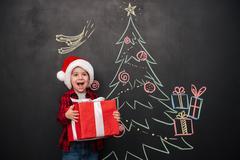Happy child holding gift near Christmas tree drawing on blackboard Stock Photos