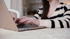 Closeup hands of young woman uses laptop in a bright dining Stock Footage