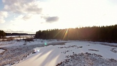 Flying over of frozen lake filling with sun light. Snow covered shores Stock Footage