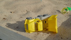 The yellow dumptruck toy on the white sand in Ireland Stock Footage