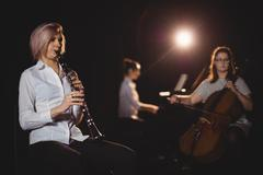 Three female students playing double bass, clarinet and piano Stock Photos