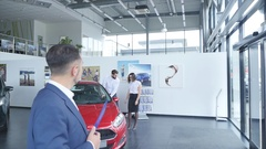 Photo of young male consultant and buyers in auto show. Consultant showing thumb Stock Footage