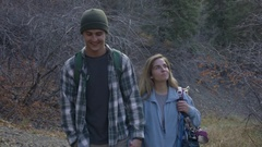 Rock Climbing Couple Hold Hands, Carry Gear, Walk Along Trail To Climbing Route Stock Footage