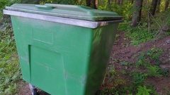 Big green trashcans in the side of the forest in Ireland Stock Footage
