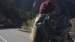OTS Steadicam Shot Of Young Woman Backpacking Down Canyon Road In Utah Stock Footage