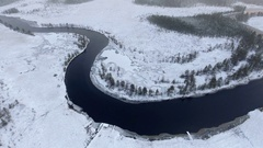 Winter river bend with open water flowing in snowy swamplands of Karelia. Aerial Stock Footage