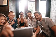 Multiracial people having fun at cafe taking a selfie Stock Photos