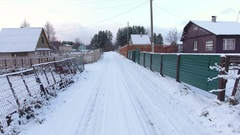 Camera moving on wintry rural road among timber houses and plots of land. Winter Stock Footage