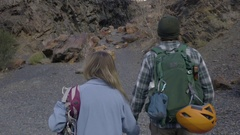 Rock Climbing Couple Hold Hands And Walk Up Trail Toward Their Climbing Route Stock Footage