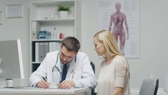 Male Doctor Writes a Prescription to His Young Female Patient and Gives it Stock Footage