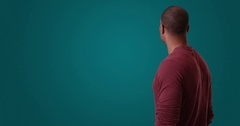 An African American man looks away from camera standing on a blue background Stock Footage