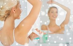 Woman with antiperspirant deodorant at bathroom Stock Photos