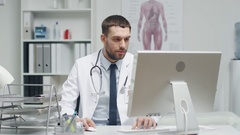 Male Doctor is Working at His Desk. He Interrupts His Work, Folds His Hands  Stock Footage