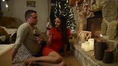 Couple sitting in front of fireplace, drinking wine Stock Footage
