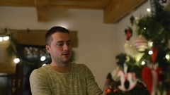 Beautiful young couple decorating Christmas tree at home Stock Footage