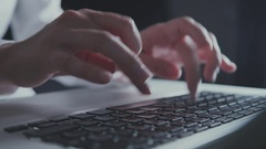 Woman hands in white blouse typing on keyboard in the evening light Stock Footage