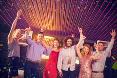 Composite image of smiling friends dancing on dance floor Stock Photos