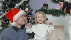 Parents kiss the cheeks of a little girl, Christmas Stock Footage