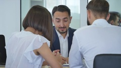 Car Dealer signing a contract to purchase and giving the key to a new car to a Stock Footage