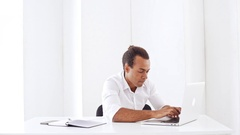 Young businessman smiling typing on laptop showing okay at workplace Slow motion Stock Footage
