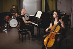 Group of students playing double bass, drum set and piano Kuvituskuvat