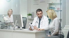 Professional Doctor Consults Mid Adult Woman. He Points out Something  Stock Footage
