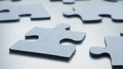 Blue jigsaw puzzle pieces on the table shallow DOF Stock Footage