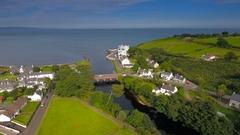 The aerial landscape shot of the greeny coastal village Cushendun in .. Stock Footage