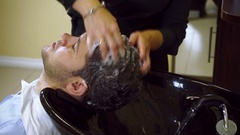 Preparing for the haircut. Female barber washing the head of a young man. HD Stock Footage