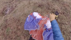 A man packs up his fabric wing after speed flying riding from the top of a mount Stock Footage