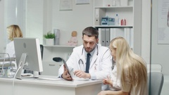 Male Doctor Consults Young Girl and Her Mother with a Help of a Tablet.  Stock Footage