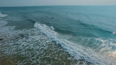 Surfers in ocean waves at sunset Stock Footage
