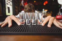 Bartender preparing and lining shot glasses for alcoholic drinks on bar counter Stock Photos