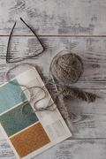 Handicraft and needlework concept - knitting needles and balls of yarn on woo Stock Photos