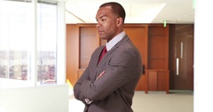 An African American businessman crosses his arms and then looks at his smart Stock Footage