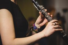 Mid-section of female student playing clarinet Stock Photos