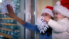 Loving woman and child girl with red santa hats glue paper snowflakes on window Stock Footage