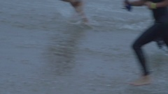 Athletes compete in a triathlon by running in from the ocean swim. Stock Footage
