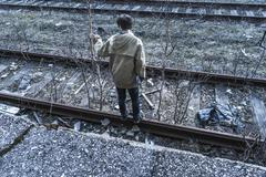 Young boy walking on railroad tracks Stock Photos